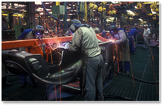 welders on a manufacturing line for truck chassis production